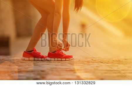 Running woman during sunny day in the city. Female fitness model training outside in city.