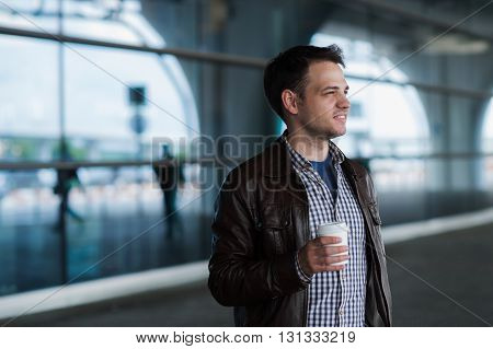 Stylish handsome young male traveller with bristle standing outdoors near the airport terminal. Man wearing jacket and shirt. Smiling person looking to camera holding cup of coffee.