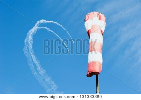 Two single-engine airplane in the sky draw a loop out of the clouds on a background of wind direction