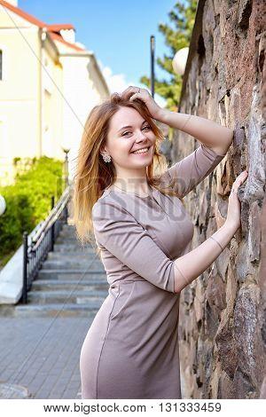 Young fashion woman in dress near stone wall. City lifestyle. Female fashion.