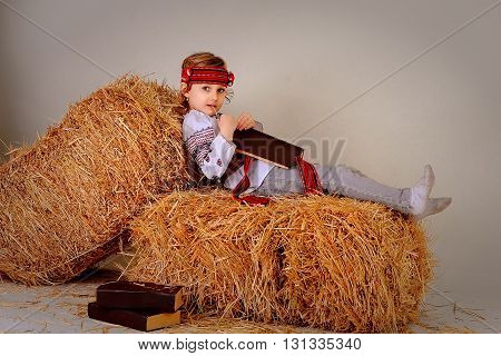 girl in national ukrainian dress and jeans with the book lies on a haystack
