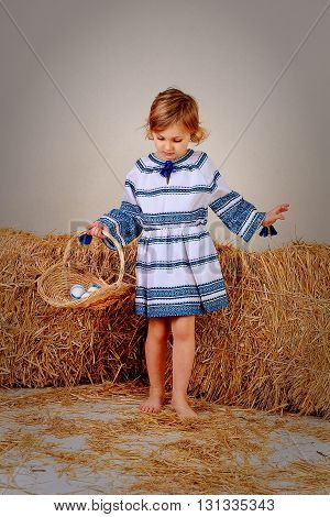 girl in national clothes goes barefoot in the snow in the studio with a basket with eggs in the hands of