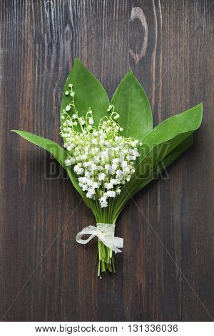 Bouquet of lilies of the valley on dark wooden background