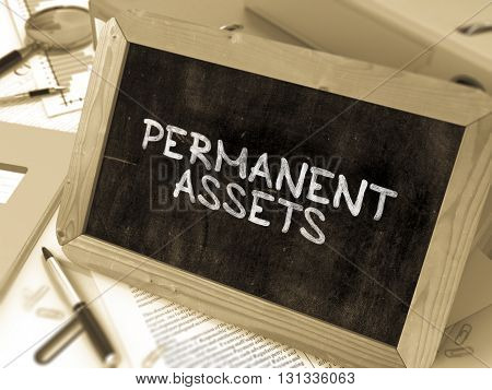 Permanent Assets - Chalkboard with Hand Drawn Text, Stack of Office Folders, Stationery, Reports on Blurred Background. Toned Image. 3D Render.