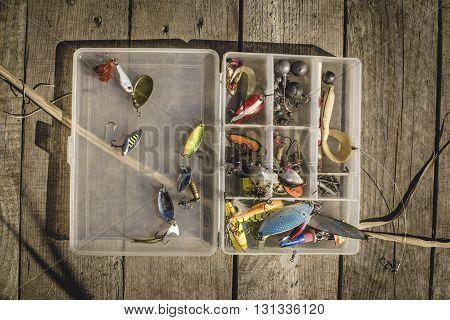 Fishing equipment in plastic box on wooden background