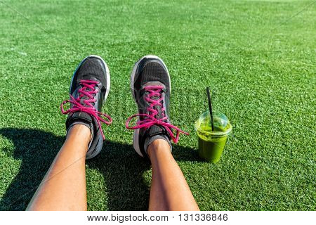 Healthy lifestyle runner girl running shoes selfie with green smoothie. Fitness woman drinking juice to go after workout in park. Healthy lifestyle sporty female athlete POV mobile phone feet picture.