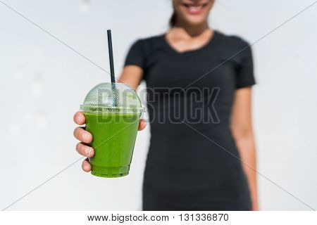 Green smoothie cup waitress woman serving drink at juice bar or cafe. Closeup of plastic take-away disposable container for restaurant business, person holding for healthy eating diet weight loss.