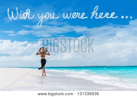 Wish you were here cloud message written in sky above woman walking on beach vacation Luxury travel Caribbean destination. Tourist relaxing on summer holiday at resort. Popular saying postcard.