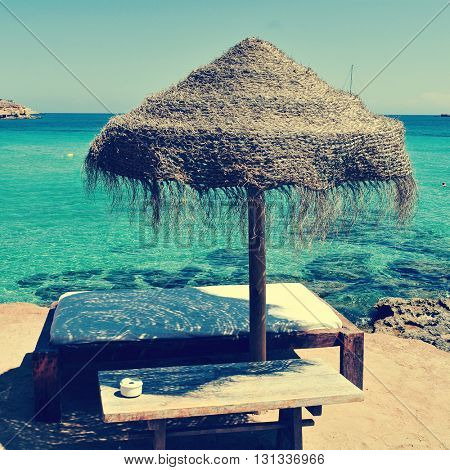 detail of a relaxing area in a beach in Ibiza, Spain, with a comfortable sunlounger and a rustic umbrella made of natural fibers, with a retro filter effect