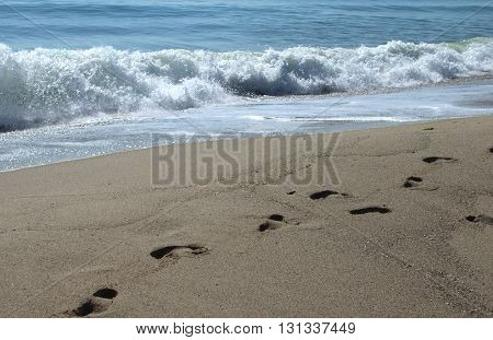 Sea shore with foamy waves and  footprints on the sand