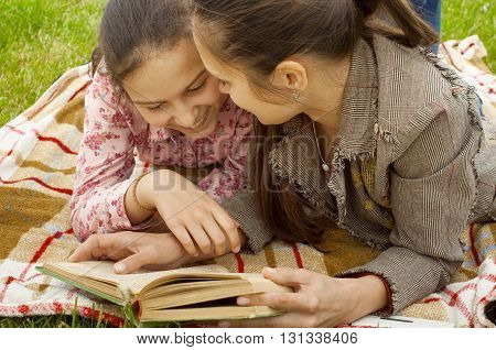 mother and daughter reading book and smiling