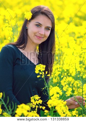 portrait of a beautiful girl in the colza field