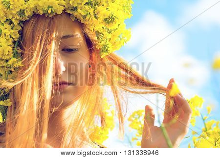 Portrait of young woman in the rape colza field