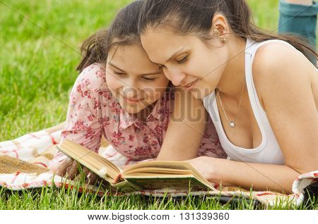 mother and daughter outdoor reading book and smiling