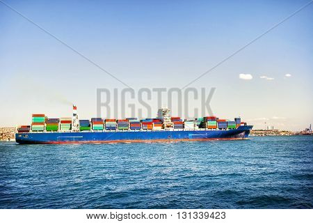 Ship loaded with colorful containers in blue sea