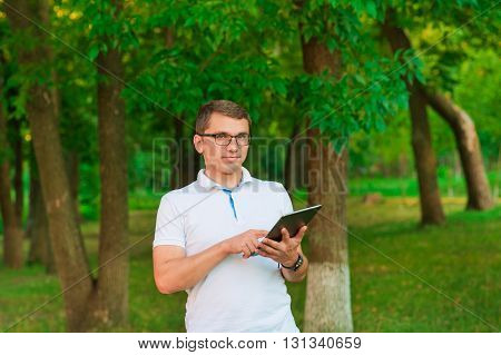 young man working with tablet computer outdoor in the park