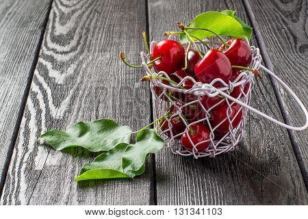 Ripe cherries in wire wicker basket on a dark wooden table