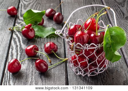 Ripe cherries in wire wicker basket on a dark wooden table. Selective focus