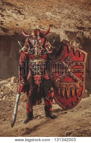 Powerful Knight In Heavy Armor With The Sword And Shield On The Dungeon Background.