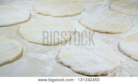 round shape of the dough with flour on the table.