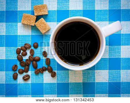 A cup of black coffee, brown sugar cubes and coffee beans on a checkered tablecloth