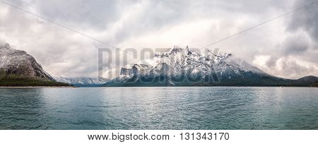 Panoramic lake view with snowy mountains and storm clouds
