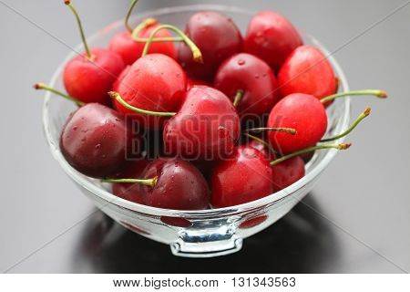 Fresh cherries in bowl on table.  Ripe red cherry berries. Sweet cherries.