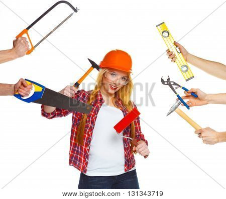 Cheerful girl builder and his hands around her with building tools in them on a white background