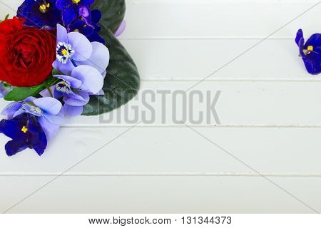 Posy of violets, pansies and ranunculus on white wooden planks background with copy space