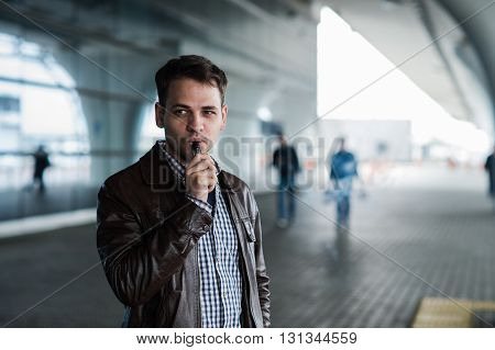 Urban lifestyle portrait of a man vaping near the airport before registration with a custom vape mod device