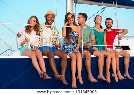 People sitting on yacht edge. Smiling young people with drinks. Value of friendship. Weekend in open sea.