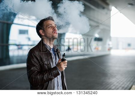Young traveller man smoking an electronic cigarette outdoor near the airport terminal.