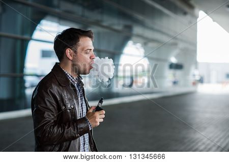 Man with a bristle smoking e-cigarette vaporizer box mode outdoors near the airport terminal before flight.