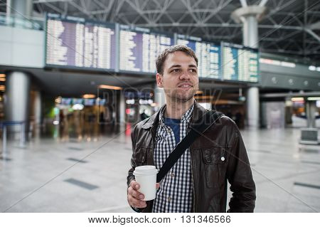Young traveller man with coffee cup at the airport over board of departures and arrivals.