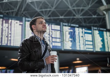 Young man in airport near flight timetable holding cup of coffee.