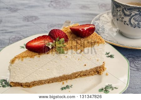 Piece of cheesecake in porcelain saucer and cup of coffee