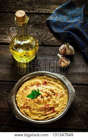 Hummus in metal bowl on dark wooden table. Selective focus. Style rustic.