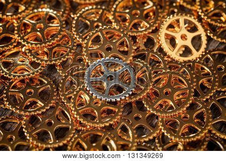 Closeup of bronze cogwheels pile with one silver