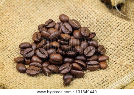 Roasted coffee beans on sackcloth background