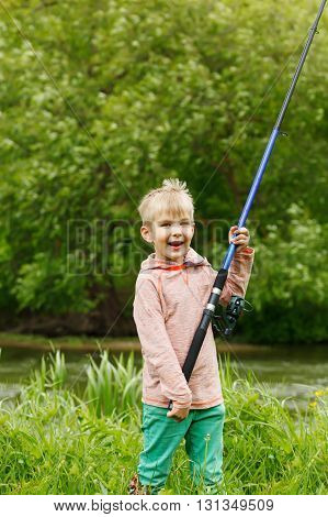 Cute Small Boy Stand Near A River With A Fishing Rod In His Hands.