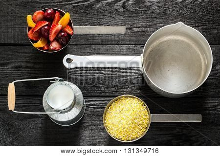 Utensils and ingredients for cooking healthy breakfast corn cereal with milk and fruit. Top view flat lay