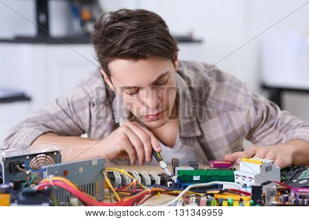 Young man working with screwdriver in service center