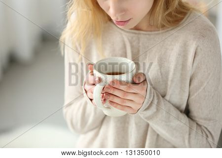 Woman in a white knitted sweater holding a cup of tea in her hands, close up
