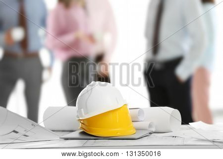 Helmets with blueprints on table and engineers on background