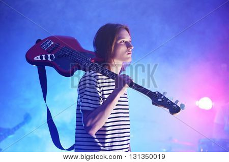Young guitarist holding his electric guitar on shoulder.