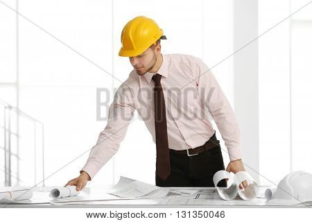 Young handsome male construction engineer working in the office