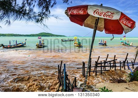 Rawai Thailand - June 13 2014: High tide floods over beach wall onto pavement during extreme high tide. Traditional long-tail boats moored in bay at Rawai beach on southern tip of Phuket southern Thailand