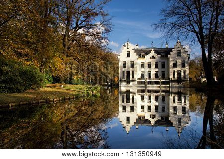 Castle Staverden reflecting in the moat and surrounded by autumn colored trees