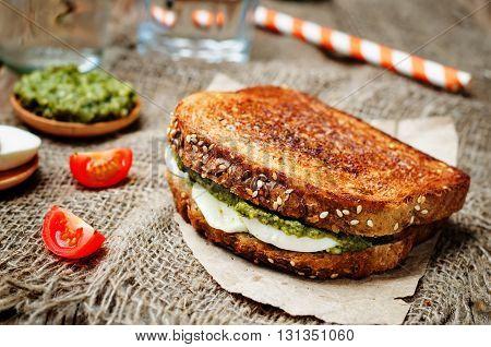 Pesto Mozzarella tomatoes grilled rye sandwich. toning.