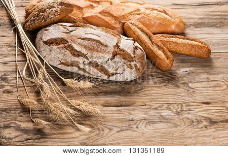 Composition with bread and ears of wheat on wooden background with space for text.
